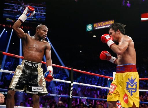 Floyd Mayweather Jr., left, celebrates during his welterweight title fight against Manny Pacquiao, from the Philippines, on Saturday, May 2, 2015 in Las Vegas.