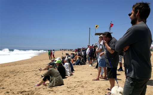 Beachgoers watch as surf breaks at The Wedge in Newport Beach, Calif., Monday, May 4, 2015.