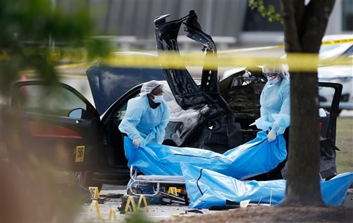Personnel remove the bodies of two gunmen Monday, May 4, 2015, in Garland, Texas. Police shot and killed the men after they opened fire on a security officer outside the suburban Dallas venue, which was hosting provocative contest for Prophet Muhammad car