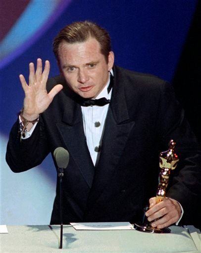 """This March 26, 1991 file photo shows Michael Blake accepting the Oscar for best adapted screenplay for """"Dances with Wolves"""" at the 63rd Annual Academy Awards in Los Angeles."""