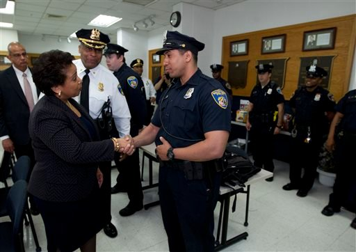 Attorney General Loretta Lynch, left, shake hands with Baltimore police officers during a visit to the Central District of Baltimore Police Department May 5, 2015, in Baltimore Md. (AP Photo/Jose Luis Magana, Pool)