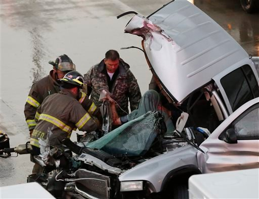 First responders work to free a passenger from a truck involved in an accident on Interstate 35 during severe weather in Moore, Okla., Wednesday, May 6, 2015. (AP Photo/Sue Ogrocki)