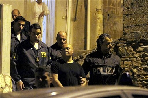 Italian Police and U.S. FBI agents take in custody a man suspected of belonging to the 'ndargheta criminal syndicate, during a police operation, in Sinopoli, southern Italy, early May 7, 2015. (AP Photo/Adriana Sapone)