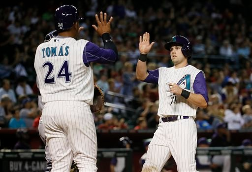 Arizona Diamondbacks' Chris Owings, right, and Yasmany Tomas celebrate after scoring on an double by Tuffy Gosewisch during the fifth inning of a baseball game against the San Diego Padres, Thursday, May 7, 2015, in Phoenix. (AP Photo/Matt York)