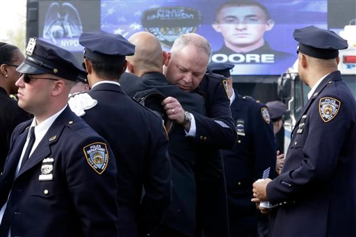 A couple of police officers embrace as they arrive for the funeral mass of New York City police officer Brian Moore, Friday, May 8, 2015, at the St. James Roman Catholic church in Seaford, N.Y. As many as 30,000 police officers from across the United Stat