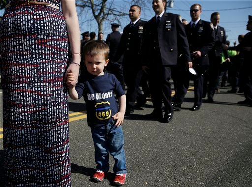 Ryan Dunne, 2, whose father works in the 105th precinct, wears a t-shirt honoring Officer Brian Moore during Moore's wake in Bethpage, N.Y., Thursday, May 7, 2015. Moore died Monday after being shot in the head while on duty Saturday. The 25-year-old and