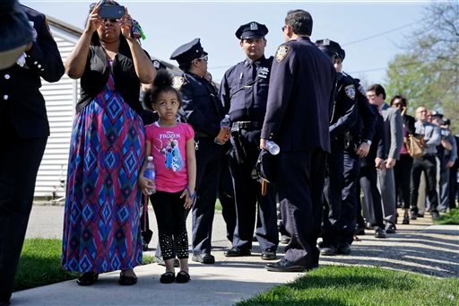 People wait in line for the wake for Officer Brian Moore in Bethpage, N.Y., Thursday, May 7, 2015. Moore died Monday after being shot in the head while on duty Saturday. The 25-year-old and his partner had stopped a man suspected of carrying a handgun whe