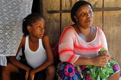 In this photo taken on Friday, May 8, 2015, Mercy Kennedy, left, sits with her caregiver Martu Weefor, right, after school at her home in Monrovia, Liberia. On the day Mercy Kennedy lost her mother to Ebola, it was hard to imagine a time Liberia would be