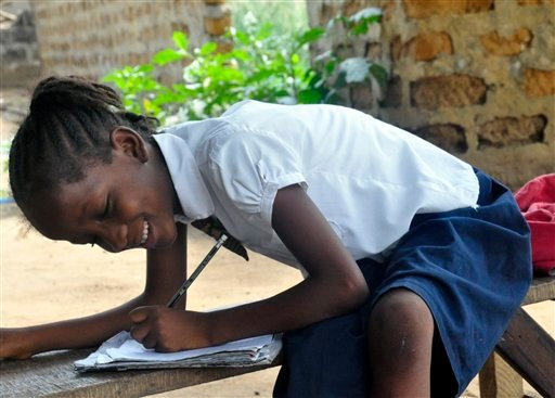 In this photo taken on Friday, May 8, 2015, Mercy Kennedy smiles as she does her home work after school at her home in Monrovia, Liberia. On the day Mercy Kennedy lost her mother to Ebola, it was hard to imagine a time Liberia would be free of one of the