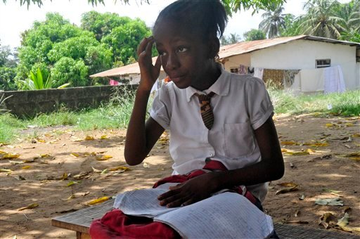 In this photo taken on Friday, May 8, 2015, Mercy Kennedy looks up as she does her homework after school at her home in Monrovia, Liberia. On the day Mercy Kennedy lost her mother to Ebola, it was hard to imagine a time Liberia would be free of one of the