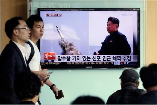 South Korean men pass by a TV news program showing images published in North Korea's Rodong Sinmun newspaper of North Korea's ballistic missile believed to have been launched from underwater and North Korean leader Kim Jong-un, at Seoul Railway station in