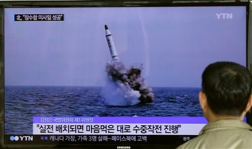A South Korean man watches a TV news program showing an image published in North Korea's Rodong Sinmun newspaper of North Korea's ballistic missile believed to have been launched from underwater, at Seoul Railway station in Seoul, South Korea, Saturday, M