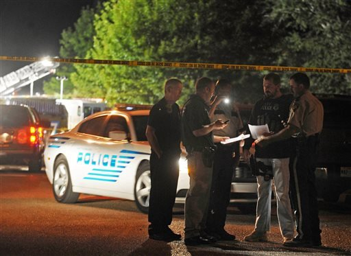 Hattiesburg lawmen study information on suspects wanted for the fatal shooting of two Hattiesburg, Miss., police officers, Saturday night, May 9, 2015. Authorities are conducting a manhunt for the suspects. (Ryan Moore/WDAM-TV via AP