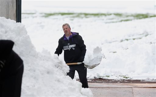 Alan Bossart, visiting clubhouse manager for the Colorado Rockies, shovels snow off the outfield in Coors Field after a wet, heavy snow Sunday, May 10, 2015, in Denver. Groundskeepers are hurrying to prepare the field for the baseball game scheduled for S