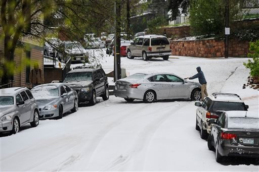 A man clears off his car after about two inches of hail fell on Manitou Springs, Colo. during a large thunderstorm Saturday, May 9, 2015. (Michael Ciaglo/The Gazette via AP)