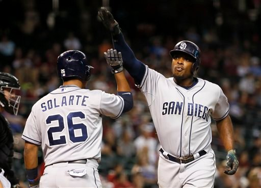San Diego Padres' Justin Upton, right, high-fives Yangervis Solarte after hitting a solo home run against the Arizona Diamondbacks during the 12th inning of a baseball game, Saturday, May 9, 2015, in Phoenix. (AP Photo/Matt York)