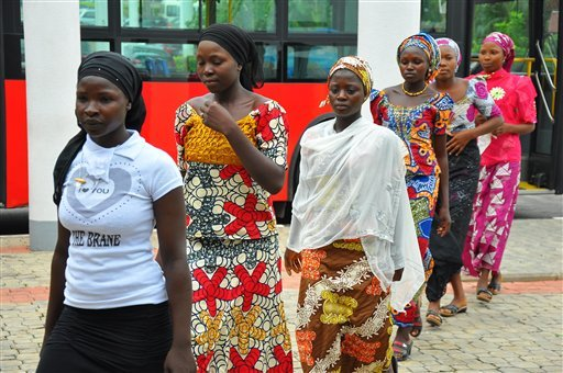 """In this file photo taken on Tuesday, July 22, 2014, school girls who escaped abduction from the Chibok government secondary school arrive for a meeting with Nigeria President Goodluck Jonathan, in Abuja, Nigeria. The taunts wouldn't stop. """"Boko Haram wive"""