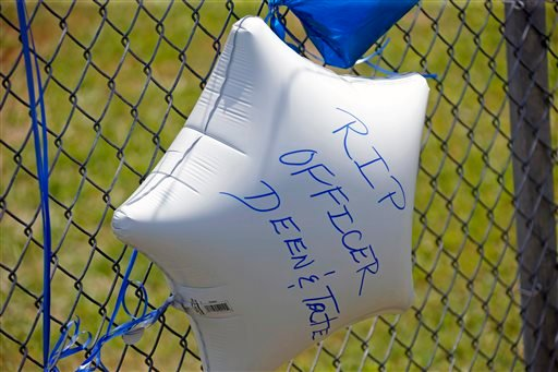 A memorial balloon with a personal message floats at a makeshift memorial in Hattiesburg, Miss., Sunday, May 10, 2015. Two officers were shot to death during an evening traffic stop turned violent, a state law enforcement spokesman said Sunday. Three susp
