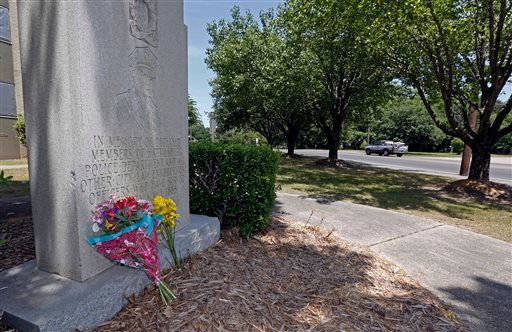 Floral arrangements rest against a police officers memorial outside a police station in Hattiesburg, Miss., Sunday, May 10, 2015. Two officers were shot to death during an evening traffic stop turned violent, a state law enforcement spokesman said Sunday.