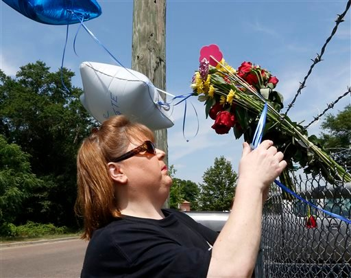 Donna Nelson of Petal, Miss., pays her respects at a makeshift memorial, near the site where two Mississippi police officers were killed, Sunday, May 10, 2015, in Hattiesburg, Miss. The officers were shot to death during an evening traffic stop turned vio