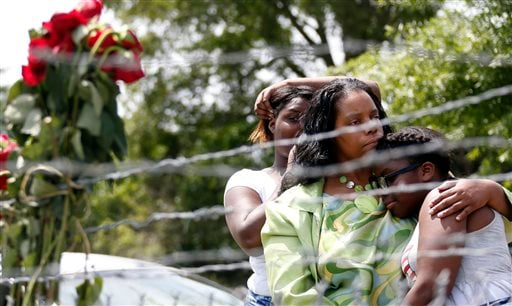 Area residents Alberta Harris, center, and Waynetta Theodore, left, and Christiena Preston, console each other as they pay their respects at a makeshift memorial, near the site where two Mississippi police officers were killed, Sunday, May 10, 2015, in Ha