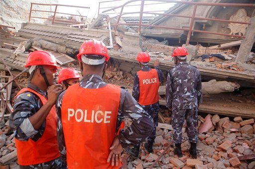A Nepalese rescue team inspects the site of a building that collapsed in an earthquake in Kathmandu, Nepal, Tuesday, May 12, 2015. A major earthquake has hit Nepal near the Chinese border between the capital of Kathmandu and Mount Everest less than three