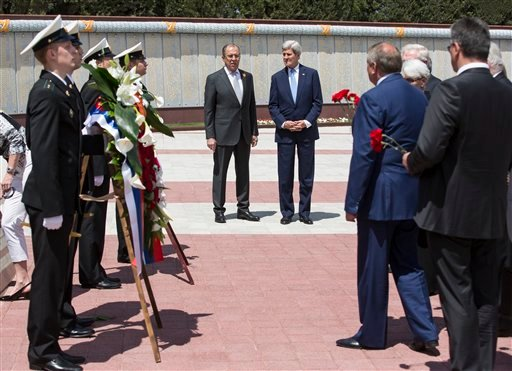 U.S Secretary of State John Kerry and Russian Foreign Minister Sergey Lavrov, center left, watch as members of the United States and Russian delegations place red flowers at the Zakovkzalny War Memorial in Sochi, Russia, Tuesday May 12, 2015. Kerry is in