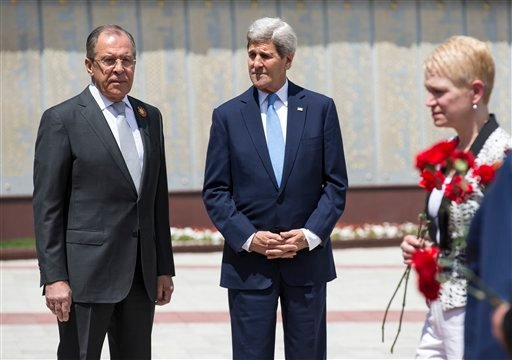 U.S Secretary of State John Kerry and Russian Foreign Minister Sergey Lavrov, left, watch as members of the United States and Russian delegations place red flowers at the Zakovkzalny War Memorial in Sochi, Russia, Tuesday May 12, 2015. Kerry is in Russia