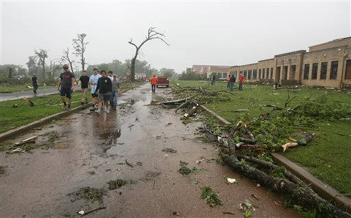 Residents of Van, Texas, make their way through storm damage near the towns Intermediate and elementary schools, Monday, May 11, 2015. Emergency responders searched through splintered wreckage Monday after a line of tornadoes battered several small commun