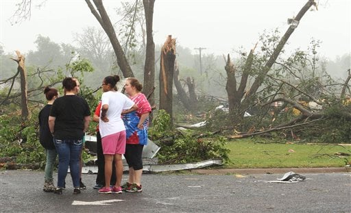 Residents survey damage near an elementary school, caused by severe weather, Monday, May 11, 2015, in Van, Texas. About 30 percent of the community was damaged from the storm late Sunday, according to Chuck Allen, fire marshal and emergency management coo