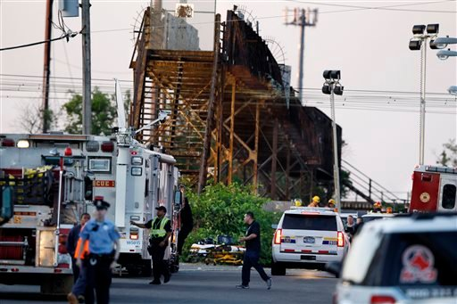Emergency personnel work on Wheatsheaf Lane near the scene of a deadly train wreck, Wednesday, May 13, 2015, in Philadelphia. An Amtrak train headed to New York City derailed and crashed in Philadelphia on Tuesday night. (AP Photo/Mel Evans)
