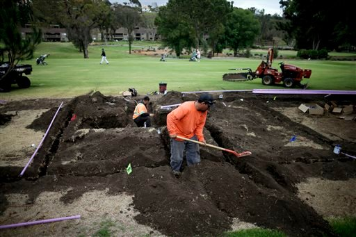 In this April 25, 2015 photo, workers install moisture monitoring and irrigation systems at the El Niguel Country Club in Laguna Niguel, Calif.