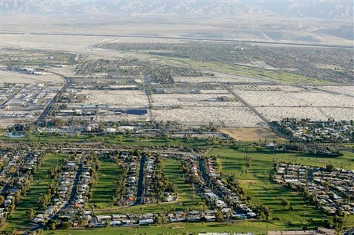 In this April 3, 2015 aerial file photo, lush green golf courses border the edge of the desert in Palm Springs, Calif.