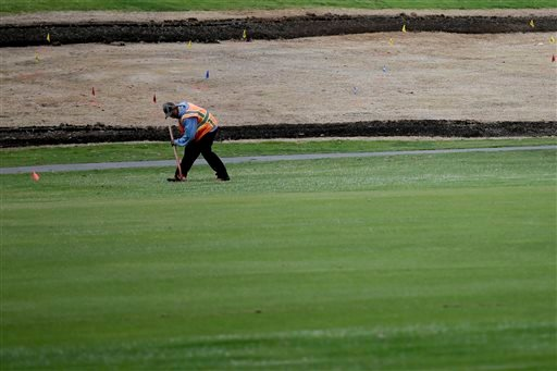 In this April 25, 2015 photo, a worker prepares an area for moisture monitoring and irrigation systems at the El Niguel Country Club in Laguna Niguel, Calif.