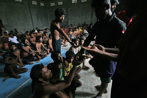 A migrant distributes sweets to others after their arrival at Kuala Langsa Port in Langsa, Aceh province, Indonesia, Friday, May 15, 2015. More than 1,000 Bangladeshi and ethnic Rohingya migrants came ashore in different parts of Indonesia and Thailand on