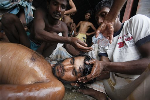Newly arrived Bangladeshi migrants pour water on the head of a man who had fainted at Kuala Langsa Port in Langsa, Aceh province, Indonesia, Friday, May 15, 2015. Hundreds of Bangladeshi and ethnic Rohingya migrants have landed on the shores of Indonesia