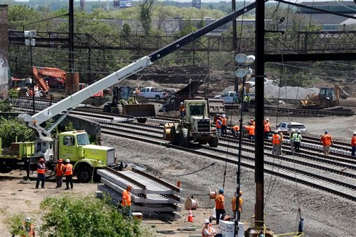 Workers labor on the site where a deadly train derailment occurred earlier in the week, Friday, May 15, 2015, in Philadelphia. Amtrak is working to restore Northeast Corridor rail service between New York City and Philadelphia. Service was suspended after