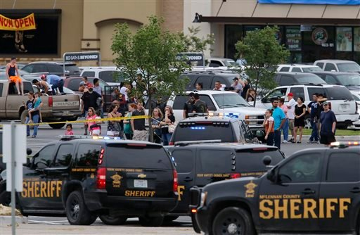 """People at the Central Texas MarketPlace watch a crime scene near the parking lot of a Twin Peaks restaurant Sunday, May 17, 2015, in Waco, Texas. Waco Police Sgt. W. Patrick Swanton told KWTX-TV there were """"multiple victims"""" after gunfire erupted between"""