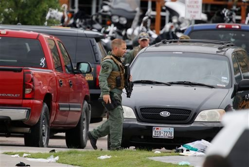"""A law enforcement officer walks past debris near the parking lot of a Twin Peaks restaurant Sunday, May 17, 2015, in Waco, Texas. Waco Police Sgt. W. Patrick Swanton told KWTX-TV there were """"multiple victims"""" after gunfire erupted between rival biker gang"""