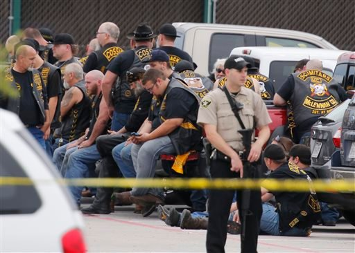 """A McLennan County deputy stands guard near a group of bikers in the parking lot of a Twin Peaks restaurant Sunday, May 17, 2015, in Waco, Texas. Waco Police Sgt. W. Patrick Swanton told KWTX-TV there were """"multiple victims"""" after gunfire erupted between r"""