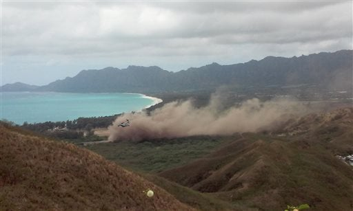 Debris rises as a Marine Corps Osprey aircraft, not pictured, makes a hard landing on Bellows Air Force Station near Waimanalo, Hawaii, Sunday, May 17, 2015. Several Marines from the aircraft were taken to a hospital, military officials say. (AP Photo/Kim
