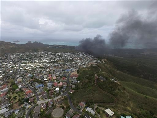 In this photo taken by a drone, smoke rises from a Marine Corps Osprey aircraft after it made a hard landing on Bellows Air Force Station near Waimanalo, Hawaii, Sunday, May 17, 2015. Several Marines from the aircraft were taken to a hospital, military of