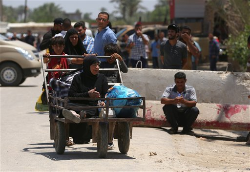 "In this Saturday, May 16, 2015 photo, Iraqis fleeing from their hometown of Ramadi walk on a street near the Bzebiz bridge, 65 kilometers (40 miles) west of Baghdad. Muhannad Haimour, a spokesman for the governor of Iraq's Anbar province, said Sunday, ""Ra"