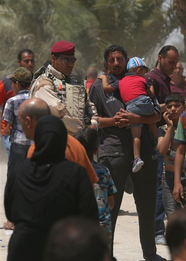 In this Saturday, May 16, 2015 photo, Iraqis fleeing from their hometown of Ramadi walk on a street near the Bzebiz bridge, 65 kilometers (40 miles) west of Baghdad. The Islamic State group seized control of the city of Ramadi on Sunday, sending Iraqi for