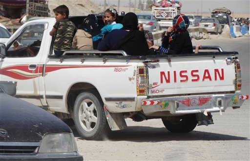 In this Monday, May 18, 2015 photo, civilians fleeing their hometown of Ramadi, Iraq, drive away a police checkpoint as they drive through Habaniyah town, 80 kilometers (50 miles) west of Baghdad. Iraqi forces and allied Sunni tribesmen repelled an Islami