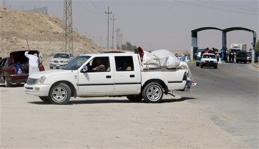 In this Monday, May 18, 2015 photo, civilians fleeing their hometown of Ramadi, Iraq, pull over their vehicle to be checked by police officers as they drive through Habaniyah town, 80 kilometers (50 miles) west of Baghdad. Iraqi forces and allied Sunni tr