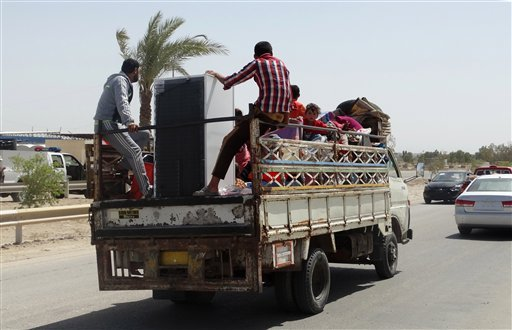 In this Monday, May 18, 2015 photo, civilians fleeing their hometown of Ramadi, Iraq, rides on a truck in Habaniyah town, 80 kilometers (50 miles) west of Baghdad. Iraqi forces and allied Sunni tribesmen repelled an Islamic State attack overnight on a tow