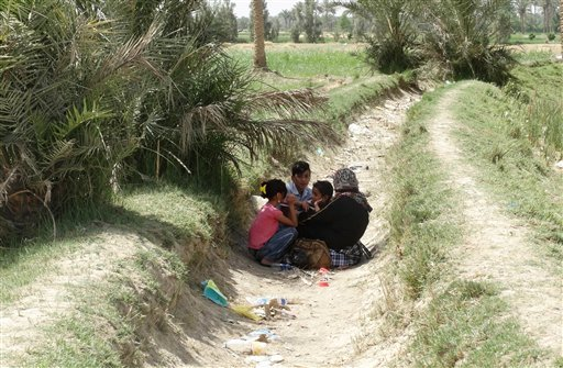 In this Monday, May 18, 2015 photo, displaced Iraqis from Ramadi wait in the open, as security forces close the Bzebiz bridge for security reasons, to prevent them from crossing to the capital, near the Bzebiz bridge, 65 kilometers (40 miles) west of Bagh