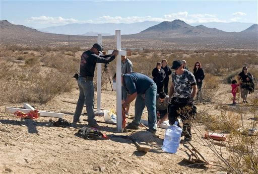 In this Nov. 20, 2013, file photo, residents of Victorville, Calif., and surrounding communities place crosses near the graves where the McStay family was found in Victorville, Calif.
