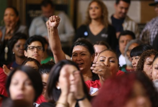 Workers react as the Los Angeles City Council votes to raise the minimum wage in the city to $15 an hour by 2020, making it the largest city in the nation to do so, in Los Angeles May 19, 2015. (AP Photo/Damian Dovarganes)
